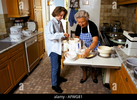 GRANDAUGHTER AND GRANDMOTHER MAKING A CAKE FOR A  COMPETITION GLOUCESTERSHIRE - Stock Photo