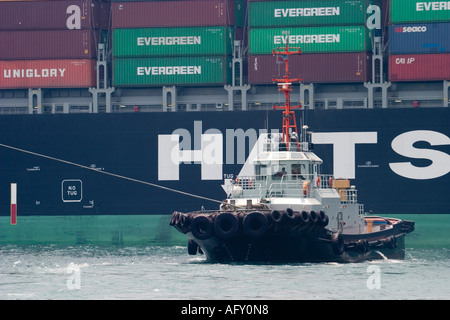 Tug boat pulls mooring line of container ship out of dock - Stock Photo