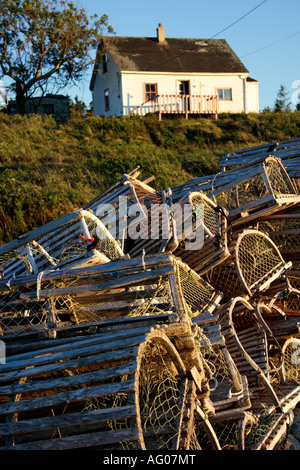 pile of old wooden lobster traps in front of vintage fishing house, Nova Scotia, Canada. Photo by Willy Matheisl - Stock Photo