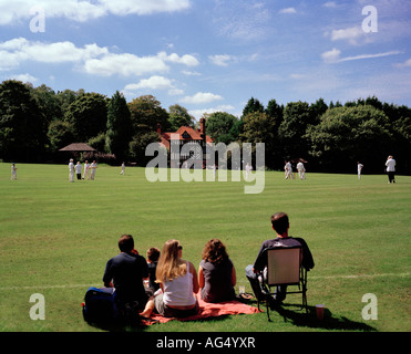 Family watching a game of village cricket Tilford Green, Surrey, England, UK. - Stock Photo