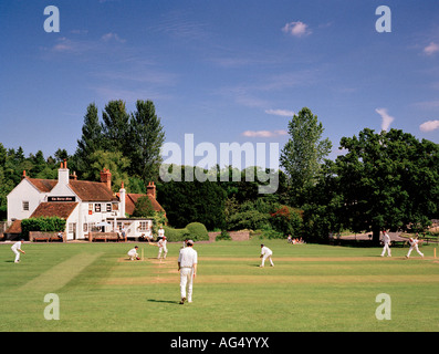 Game of village cricket Tilford Green, Surrey, England, UK. - Stock Photo