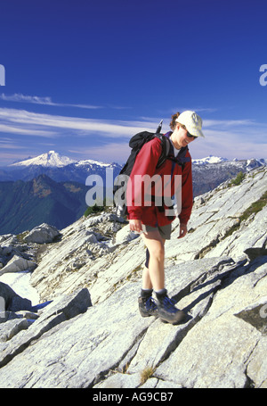 Hiker in red jacket scrambling up rocky slabs Mt Baker in background North Cascades National Park Washington - Stock Photo