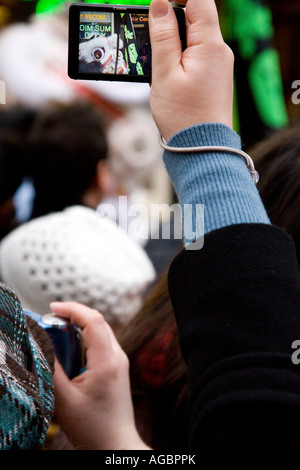 Woman in crowd taking pictures of Dragon dance during Chinese New Year celebrations in Chinatown London 2007 - Stock Photo