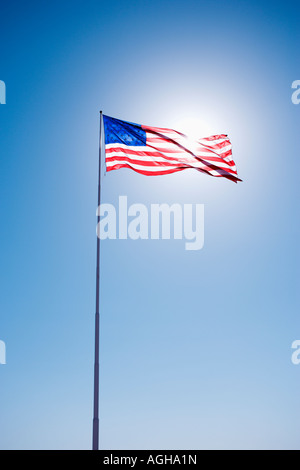 American flag blowing in clear blue sky - Stock Photo