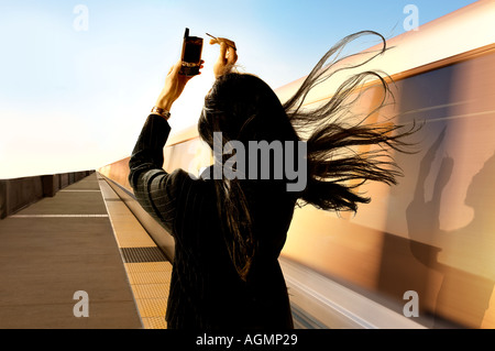 Woman works on PDA cellphone as a commuter train speeds nearby blowing her long hair into the camera - Stock Photo