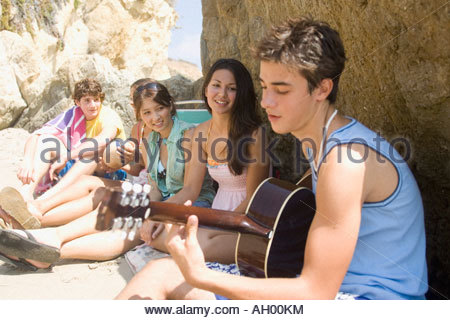 Teenage boy playing guitar for friends on beach - Stock Photo