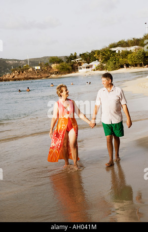 Mature woman holding a senior man's hand and walking on the beach - Stock Photo