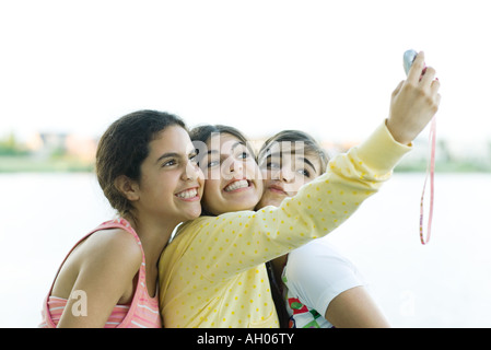 Young female friends taking photo of selves with cell phone - Stock Photo