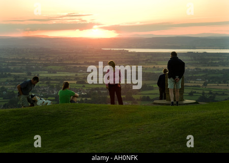 A family watching the sunset from the Cotswold viewpoint on Frocester Hill adjoining Coaley Peak Picnic Site, Gloucestershire - Stock Photo