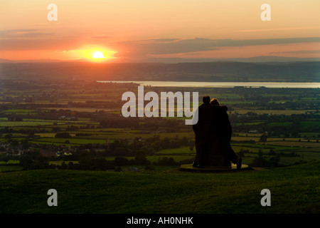 A couple watching the sunset from the Cotswold scarp viewpoint Frocester Hill adjoining Coaley Peak Picnic Site, - Stock Photo