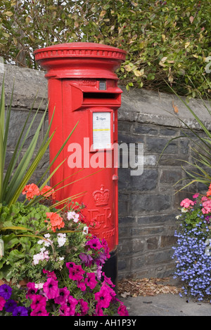 Britain UK Red Royal Mail pillar box by wall with colourful flower display - Stock Photo