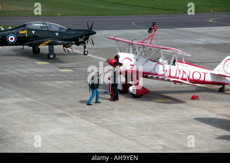 Member of the Guinot Wingwalking Display Team being photographed in front of plane at Shoreham Airport, West Sussex - Stock Photo