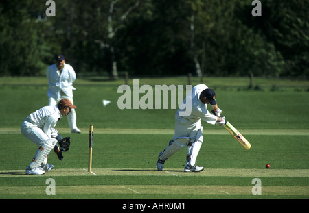 Batsman in action during village cricket match at Wellesbourne, Warwickshire, England, UK - Stock Photo