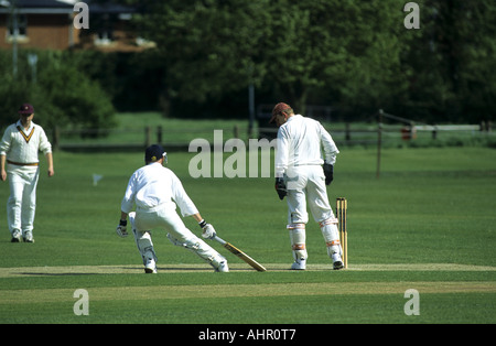 Batsman touching crease during village cricket match at Wellesbourne, Warwickshire, England, UK - Stock Photo