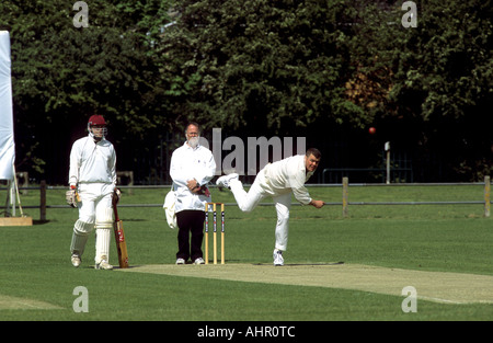 Bowler in action during village cricket match at Wellesbourne, Warwickshire, England, UK - Stock Photo