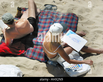 Caucasian couple in swimwear seen from above relaxing on the beach turned away from each other with the lady drawing - Stock Photo