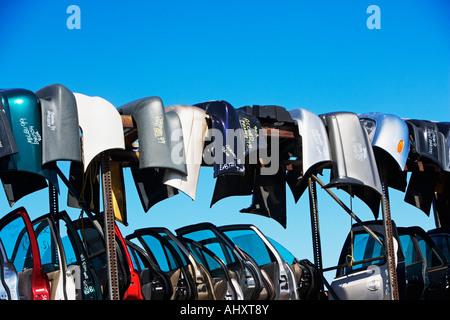 Car doors and bumpers at junkyard - Stock Photo