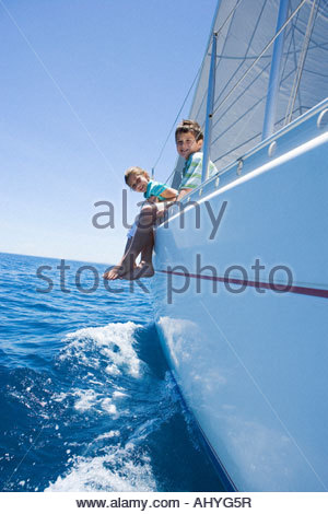 Boy and girl  sitting on deck of sailing boat out to sea, feet dangling over side, smiling, side view, portrait - Stock Photo