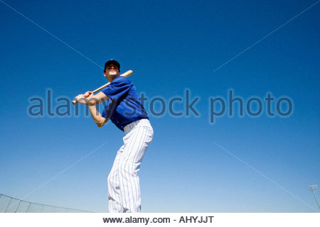 Baseball batter, in blue uniform, preparing to hit ball during competitive game, front view, low angle view tilt - Stock Photo