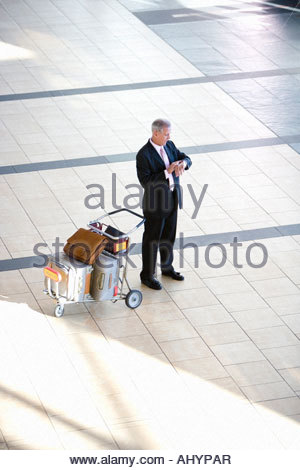 Senior businessman standing beside luggage trolley in airport, checking time on wristwatch, elevated view - Stock Photo