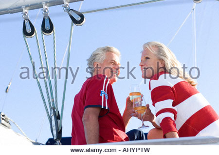 Mature couple, in jumper and t-shirt, sitting on deck of yacht moored at harbour jetty, holding glasses filled with - Stock Photo
