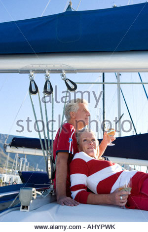 Mature couple, in red jumper and t-shirt, sitting on deck of yacht moored at harbour jetty, drinking white wine - Stock Photo