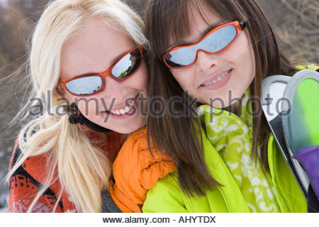 Two young women with skis in snow, wearing sunglasses, smiling, portrait, close-up - Stock Photo
