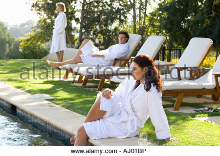 Young woman wearing white robe sitting by swimming pool with legs in water, man and woman on deck chairs in background - Stock Photo