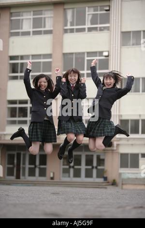 Three high school girls jumping in schoolyard - Stock Photo