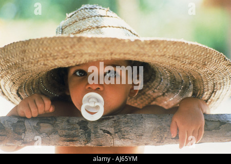 Young Brazilian boy or cowboy with pacifier under big straw hat or sombrero - Stock Photo