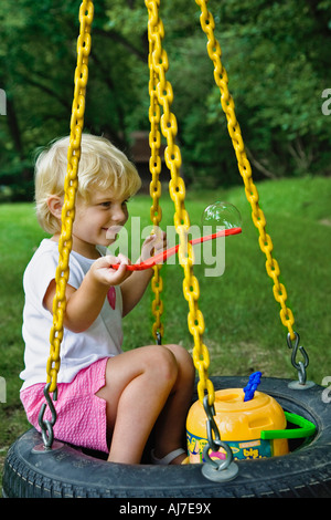 Young girl blowing bubbles on tire swing. - Stock Photo