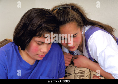 Tongan American sisters age 13 and 16 reading in their home. St Paul Minnesota USA - Stock Photo