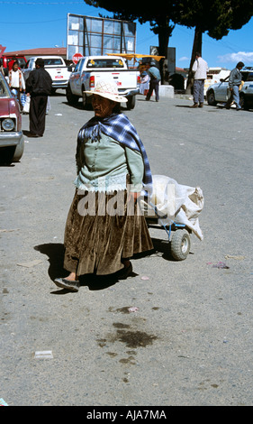 Lady pulling trolley, Kasani border crossing, Bolivian side of Peru and Bolivia border, Bolivia - Stock Photo