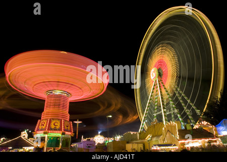 chairoplane and big wheel on the Cranger fair at night, Germany, Ruhr Area, Herne - Stock Photo