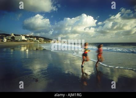 Two woman running along Laguna Beach shore in Southern California at sunset - Stock Photo