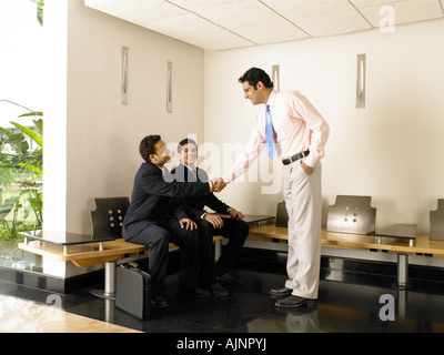 A man shaking hands with two men in the office lobby - Stock Photo