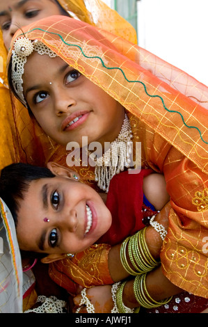 Vertical close up of two young girls hugging each other dressed in their best saris at the Ugadi Festival. - Stock Photo