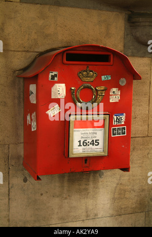 Traditional red post mail box with bugel and crown insignia and stickers, Brussels, Belgium, Europe - Stock Photo