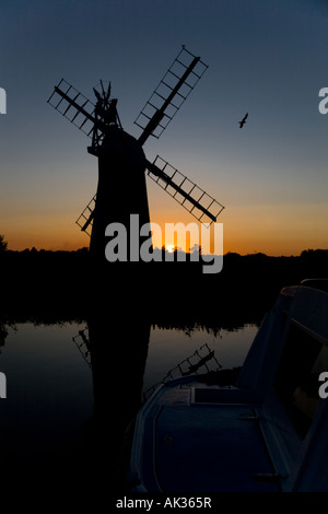 Turf Fen Mill at sunset with Broads boat in foreground, Norfolk Broads, UK - Stock Photo
