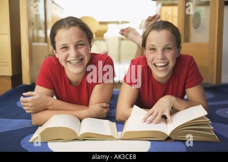 Twin teen girls smile while doing their homework - Stock Photo
