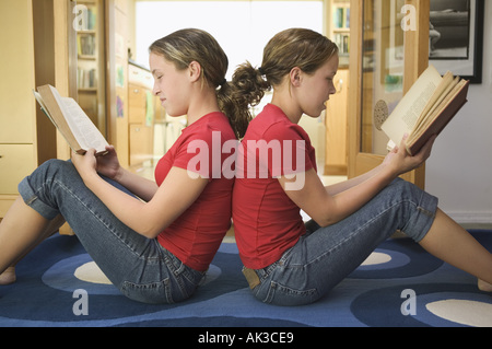 Teenage twin girls sit back to back while reading - Stock Photo