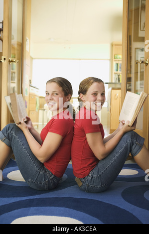 Young twin Caucasian teenage girls wearing red shirts sit back to back on a blue rug holding books - Stock Photo