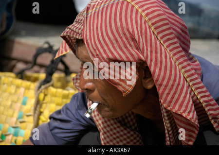 Portrait of a man wearing a kerchief smoking a joint Water Festival Phnom Penh Cambodia - Stock Photo