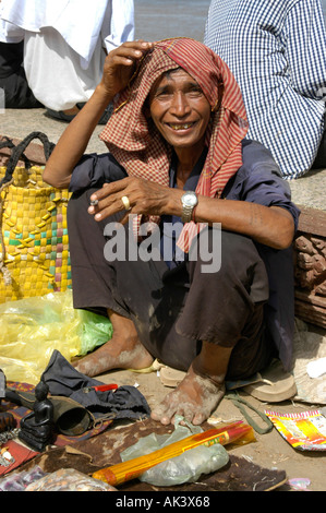 Man selling small souvenirs wearing a kerchief smoking a joint Water Festival Phnom Penh Cambodia - Stock Photo