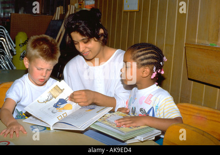 East Indian girl age 19 reading book with two children age 5. St Paul Minnesota USA - Stock Photo