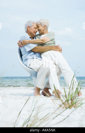Senior couple sitting in chair together on beach with foreheads touching, woman sitting on man's lap - Stock Photo