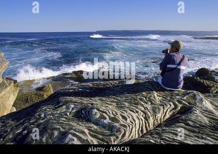 Man with a camera sitting on rocks on a beach Kurnell NSW Australia - Stock Photo