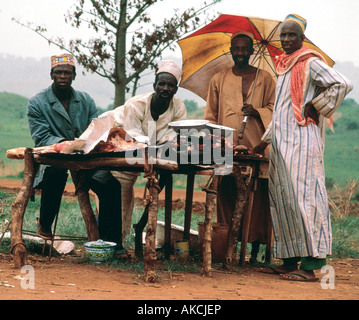 Four African men selling meat at a road side stall in the north of the Republic of Togo West Africa - Stock Photo