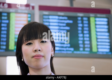 Portrait of a businesswoman in front of an arrival departure board - Stock Photo