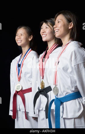 Three young women standing with their medals and smiling - Stock Photo